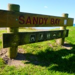 "Like RSA, NZ has a ""Sandy Bay"". Unlike RSA, it is not a nudist beach."